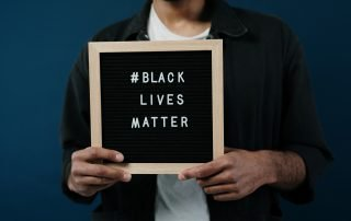 "Person dressed in dark colours holding up a sign board that displays ""#Black Lives Matter"""