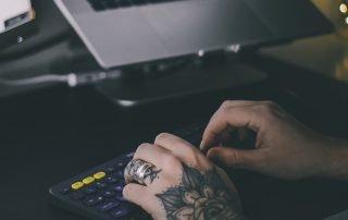 tattooed-hands-typing-on-office-keyboard