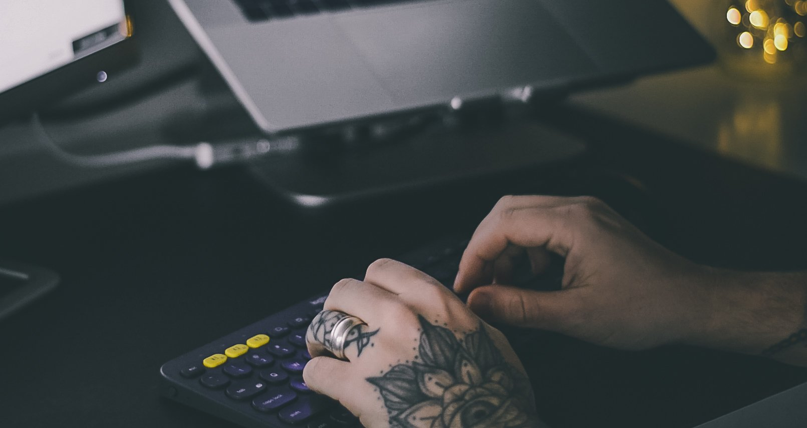tattooed-hands-typing-on-office-keyboard