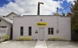 """""""Silence"""" spray painted on a white building"""