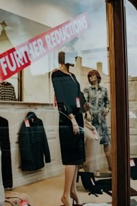 Window display with mannequins and clothing for sale