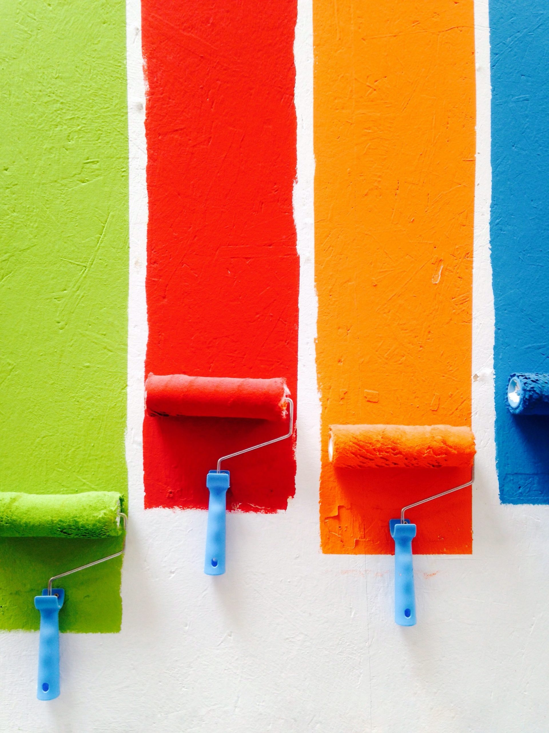 Four paint rollers applying paint to a white wall