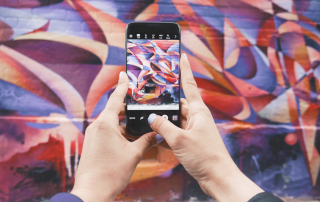 Two hands taking a picture on a cell phone of graffiti art