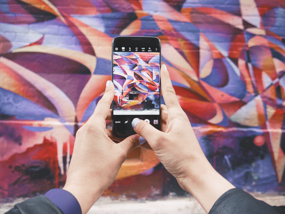 Closeup of person photographing graffiti art on a cell phone