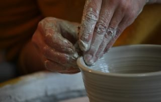 A close-up of two hands creating pottery