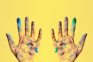 Two hands covered in paint in front of a yellow background