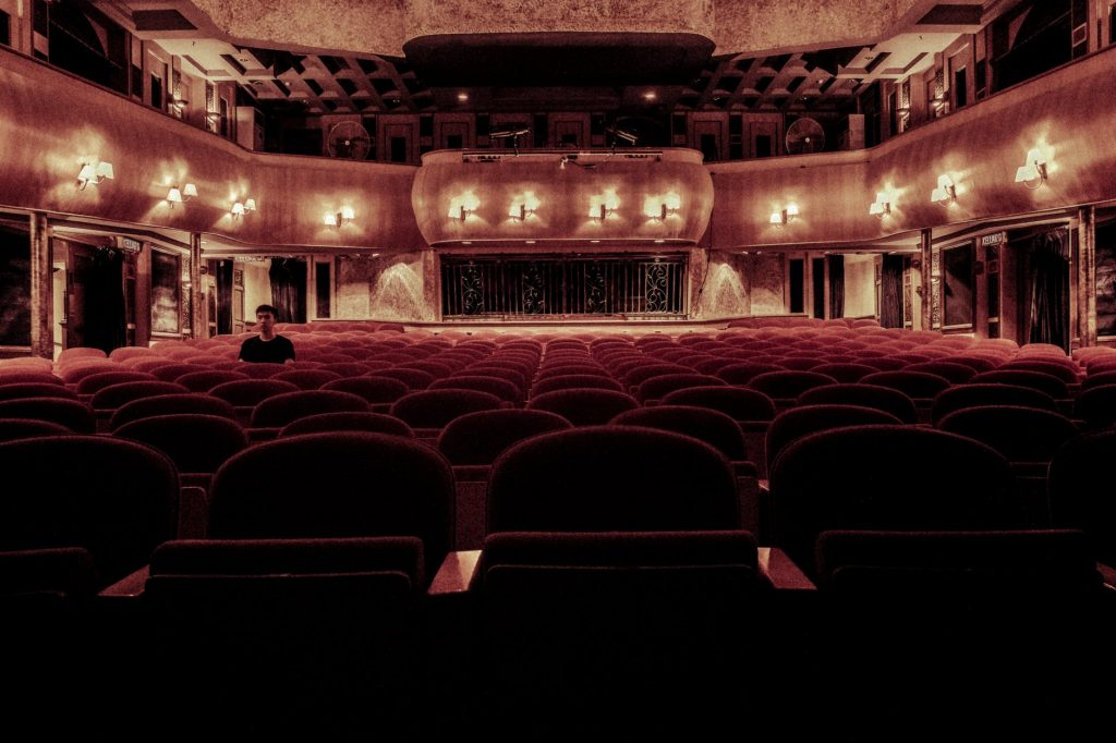 An empty theatre with one person seated near the back
