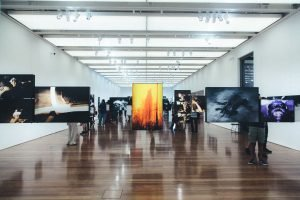 Art Gallery with images hung and people looking at them