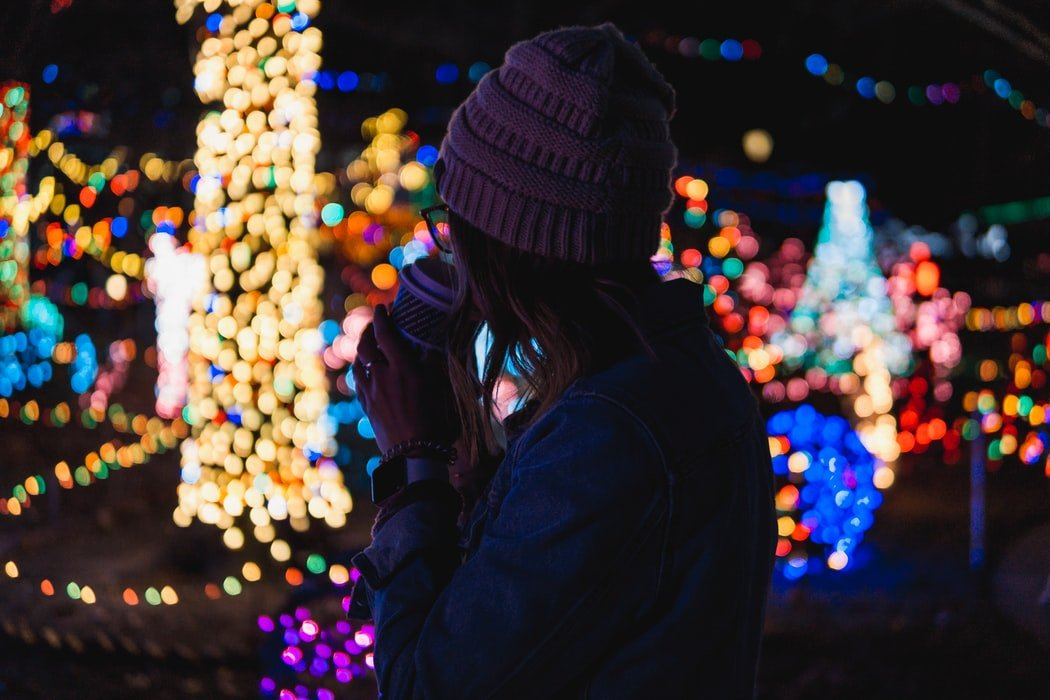 Single person dressed warmly for cold weather and drinking a hot drink against a backdrop of seasonal lights