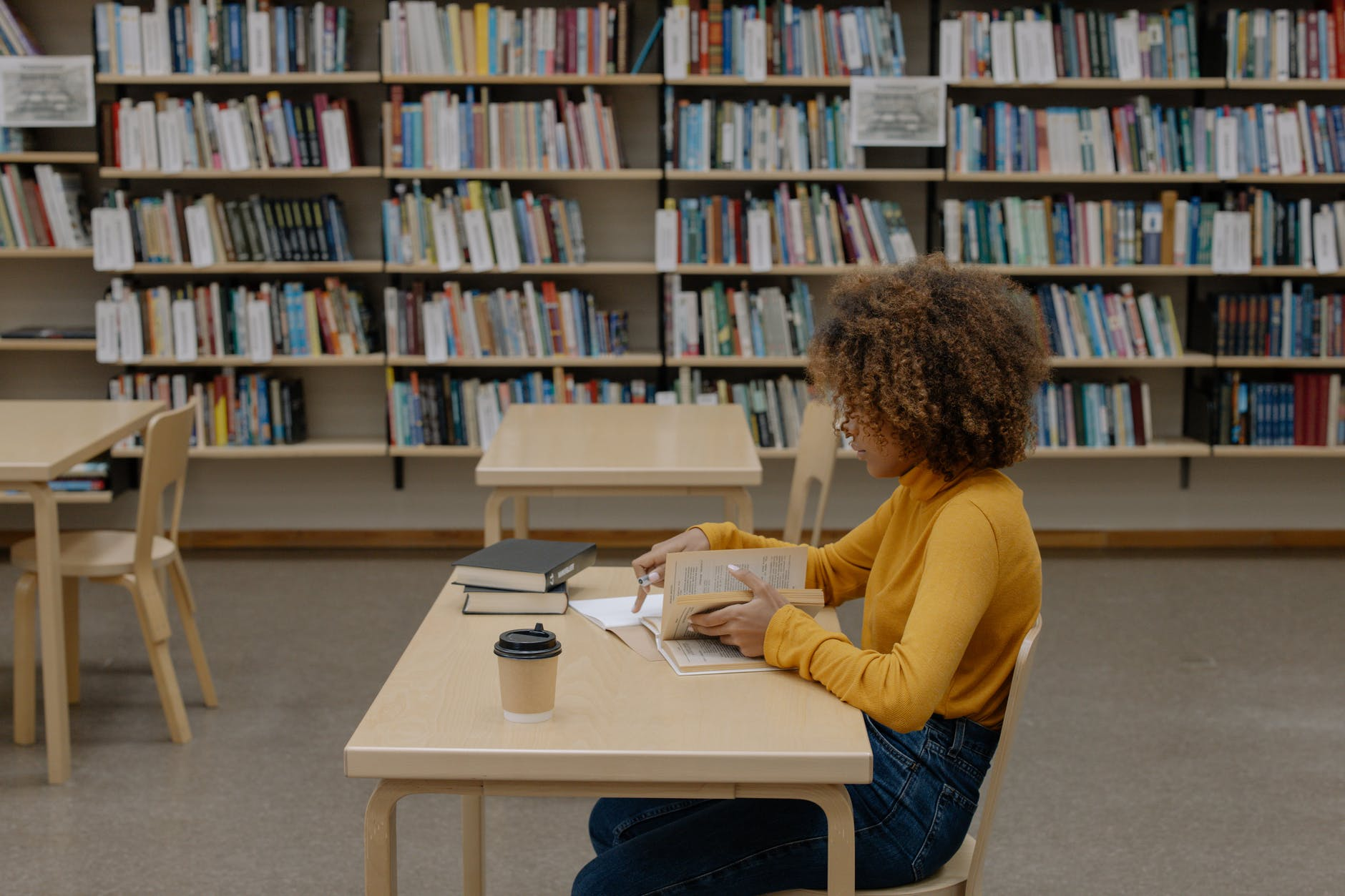 Young person studying at a desk, in a library