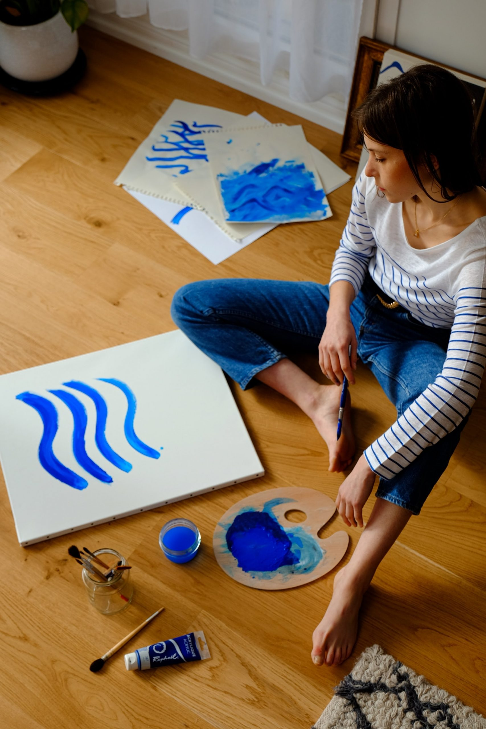 Artist trying out bright blue paint on canvas and paper