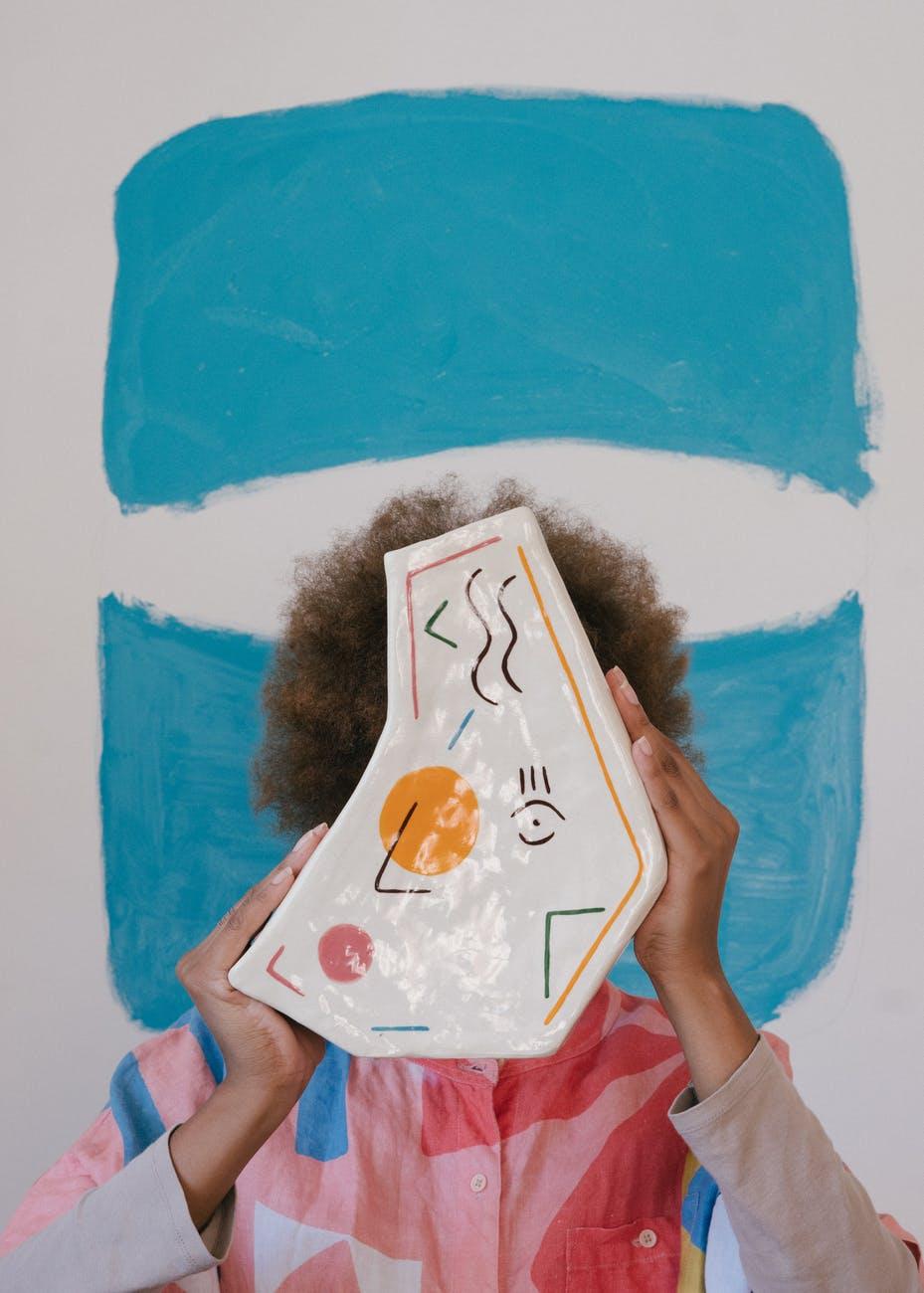 Artist holding up ceramic art