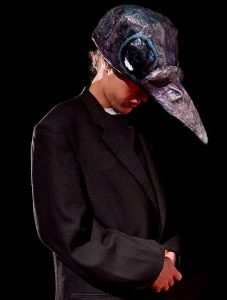 actor wearing all black with a crow head