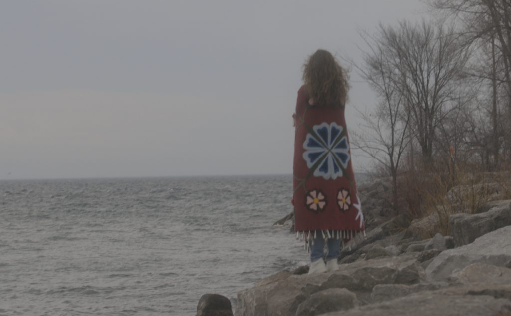 Bekah Brown wrapped in Nikonaas, a blanket that she created at the beginning of the Unmute Artist Residency, standing on the rocky shore of Trillium Park, looking out at Lake Ontario.