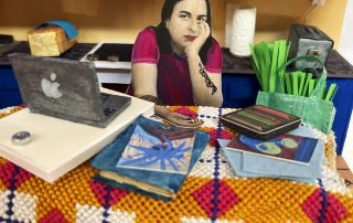 closeup of Shazia's diorama featuring a miniature self portrait sitting at the kitchen table with a laptop and art materials laid out on it, there is also a bag of groceries on a chair beside them.