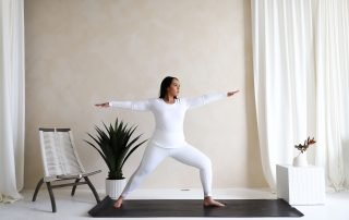 Brittany Lynn Martin dressed in white athletic wear, in a warrior pose