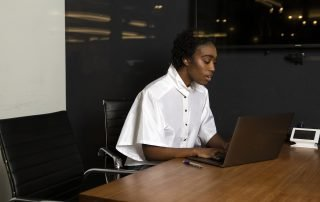 A non-binary person using a laptop at work
