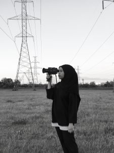Black and white profile picture of Niya in a field holding a camera to her eye
