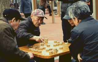 Elderly men playing Chinese Chess (XiangQi) in Chinatown.