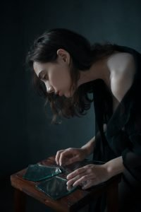 A women puts broken pieces of glass together