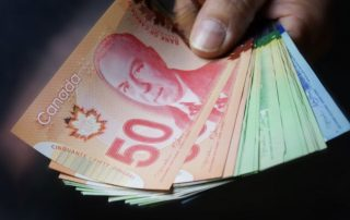 Hand holding Canadian dollar bills